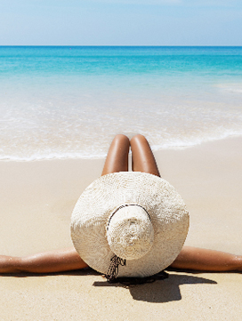 Target image depicting luxury represented by a lady on the beach tanning in the sun